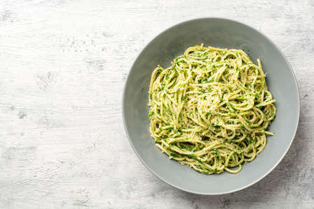 Spaghetti pasta with spinach sauce and parmesan cheese