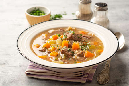 Beef and barley soup with celery, carrot and onion in plate Standard-Bild