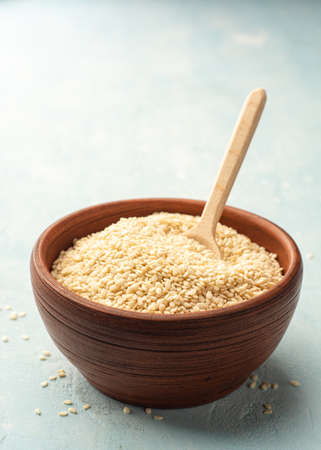 White sesame seeds in ceramic bowl with wooden spoon Standard-Bild