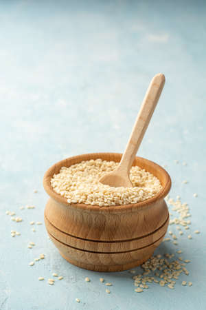 White sesame seeds in wooden bowl with wooden spoon
