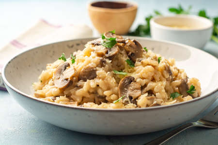 Risotto with mushrooms, parmesan cheese and parsley in plate