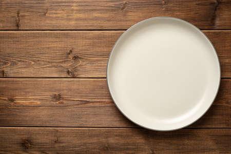 Empty plate on wooden table Standard-Bild