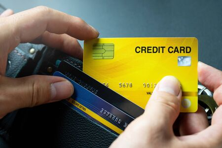 Pick yellow credit card from black wallet background