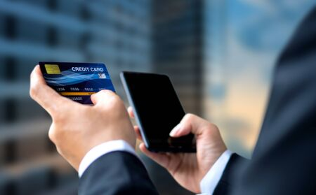 Businessman pay or shopping by credit card with smartphone Фото со стока