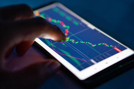 Man touch candlestick chart from stock market on smartphone screen