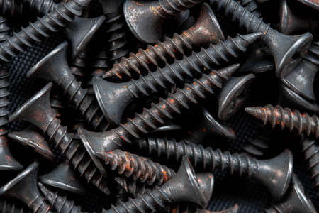 Stack of black stainless steel screw, equipment construction background