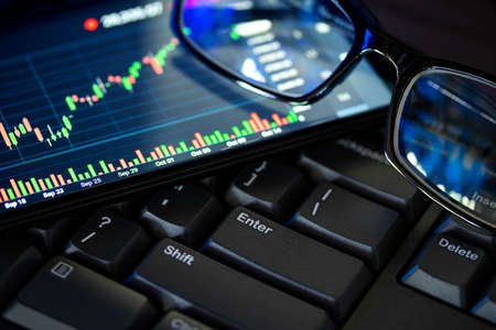 Stock market chart screen on keyboard computer and eyeglasses, online investment concept