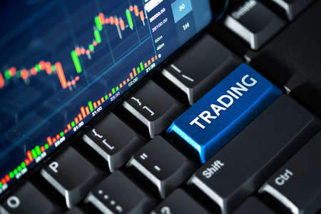 Stock market chart screen on keyboard computer and blue trading button, online investment concept