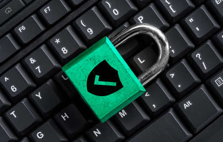 Green master key on black keyboard, computer security privacy concept Stock Photo