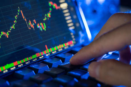 Stock market chart screen on keyboard computer and fingers touch, online investment concept Stock Photo