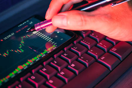 Stock market chart screen on keyboard computer and hand hold pen, online investment concept Stock Photo