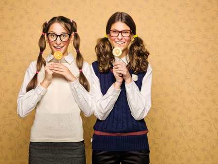 kitsch: Young female nerds with lollypop Stock Photo