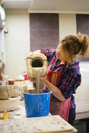 Pottery artist pouring clay