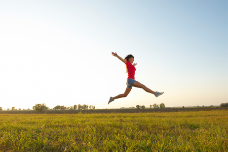 raised arms: Young woman with raised arms outdoor jumping Stock Photo