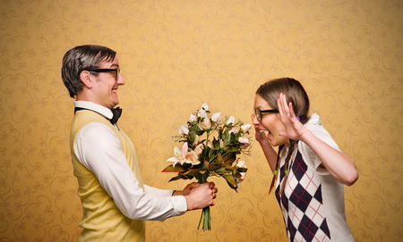 mujer fea: Nerd hombre que da las flores a empollón femenino Foto de archivo