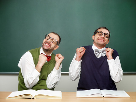 nerd glasses: Two male nerds in extasy in front of blackboard Stock Photo