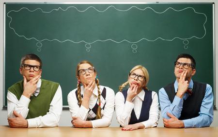 Vier nerds voor schoolbord denken Stockfoto