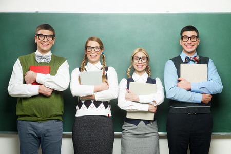 Group of nerds holding books in front of the blackboard