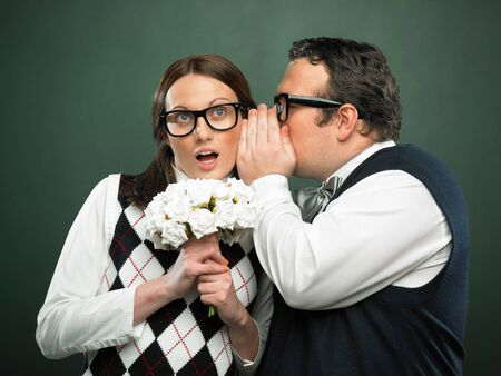 funny glasses: Nerd couple is holding flowers, he is whispering something Stock Photo