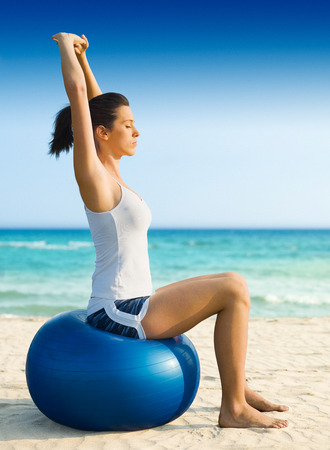 balance ball: Girl doing pilates on the beach