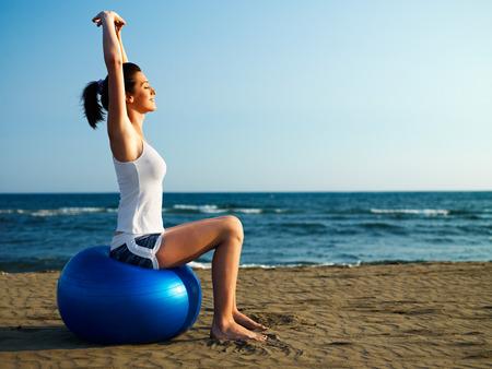 Girl doing pilates on the beach Stock Photo - 35417083
