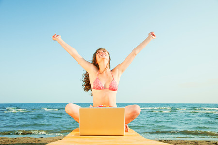 Woman sitting at beach with laptop in front of her Stock Photo