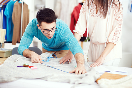 textile designer: Designer measuring textile material