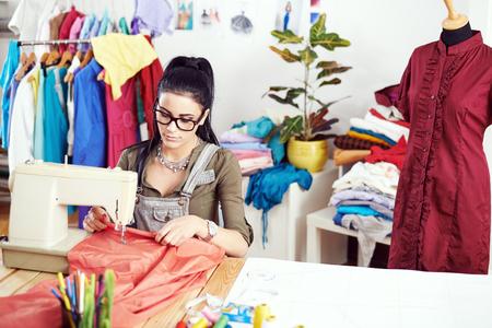 maquinas de coser: Joven diseñador de moda trabajando en la máquina de coser Foto de archivo