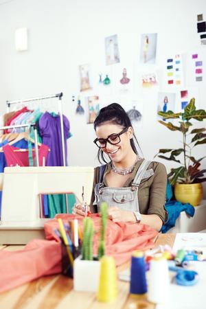 fashion design: Young female fashion designer working on sewing machine