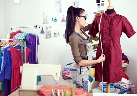 Young female designer measuring dress