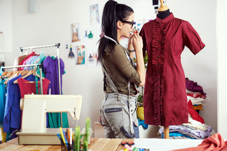 alteration: Young female designer putting needles in dress
