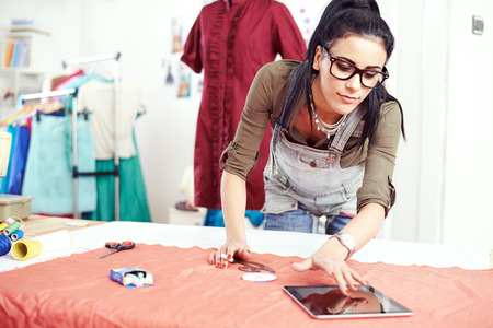 alteration: Young female designer looking tablet