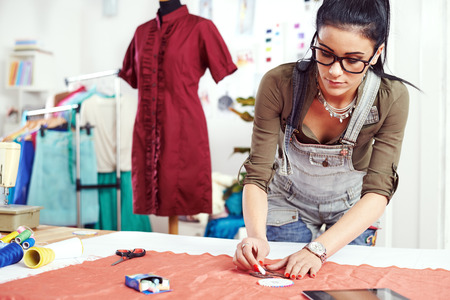 Young female designer drawing on the material Stock Photo