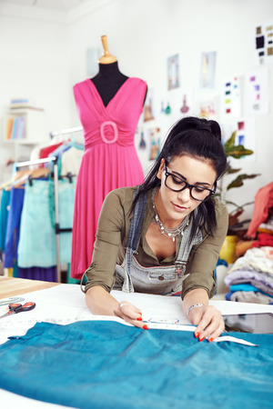 alteration: Young female designer measuring textile material