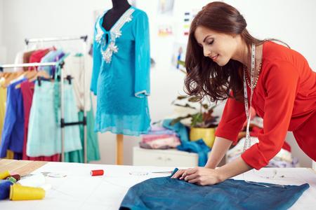 textile designer: Young female designer measuring textile material