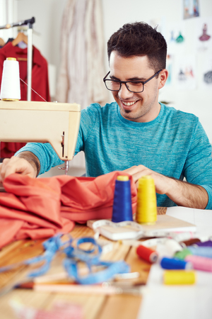 Young male fashion designer working on sewing machine