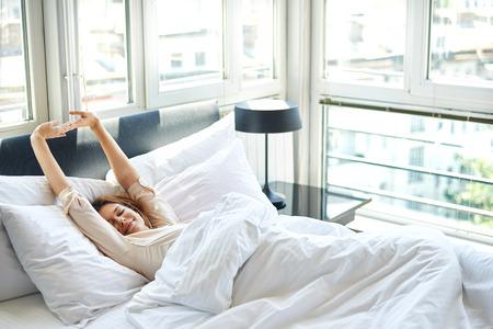 라이프 스타일: 침대에서 스트레칭 여자 스톡 콘텐츠