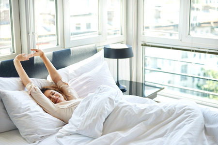 up wake: Woman stretching in bed