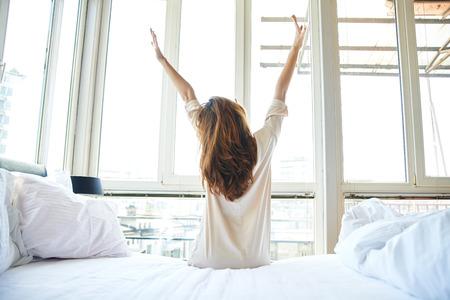 chambre à coucher: Femme étirement dans le lit, vue de dos Banque d'images