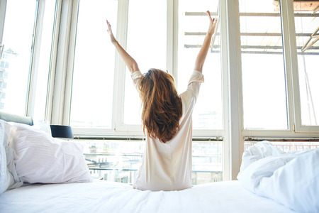 up wake: Woman stretching in bed, back view Stock Photo