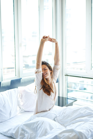 early morning: Woman stretching in bed