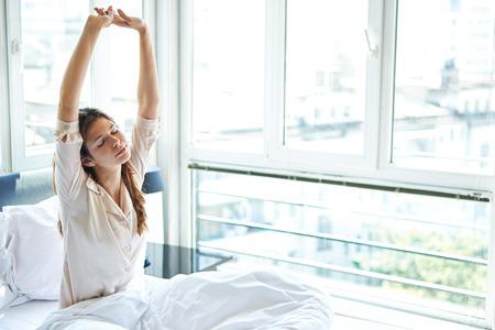 despertarse: Mujer que estira en la cama