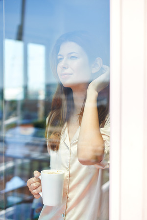 Young woman standing behind glass of balcony door, drinking morning coffee
