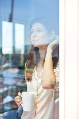 tomando café: Joven mujer de pie detrás de un cristal de la puerta del balcón, bebiendo café de la mañana Foto de archivo
