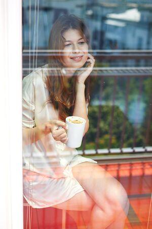 balcony door: Young woman sitting behind glass of balcony door, drinking morning coffee