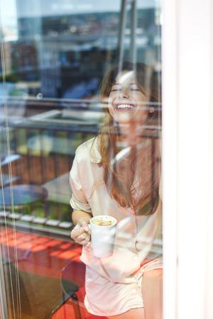 balcony door: Young woman standing behind glass of balcony door, drinking morning coffee