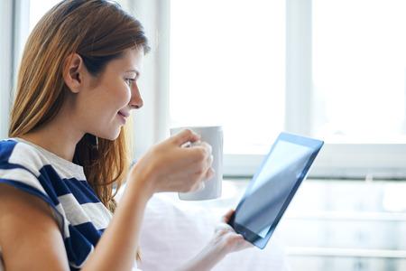 커피를 마시고 침대에서 디지털 태블릿을 읽는 젊은 여성