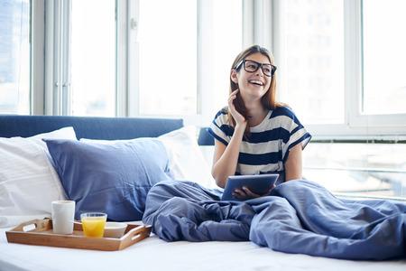 colazione: Giovane donna lettura tavoletta digitale a letto Archivio Fotografico