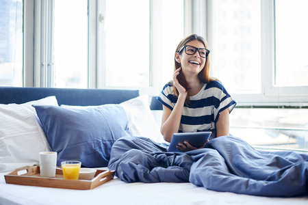 lifestyle: Jeune femme lisant tablette numérique dans son lit