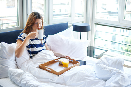 breakfast: Joven mujer bebiendo café y leyendo tableta digital en la cama
